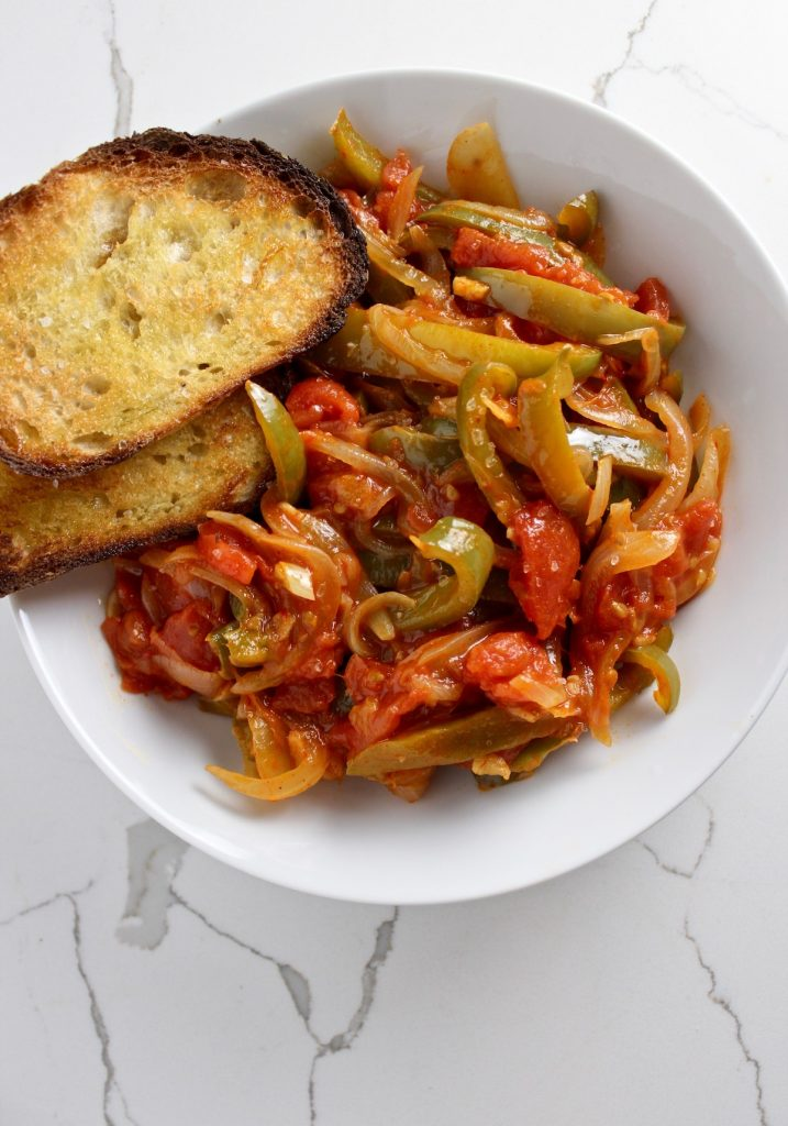 Top down shot of piperade in a white bowl with two pieces of toast