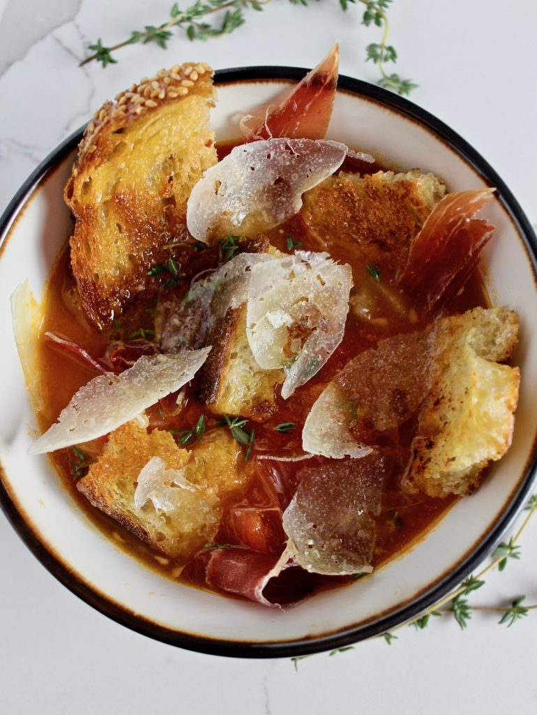 Top down shot of Tomato Soup with Jamón and Manchego in a bowl on a white countertop