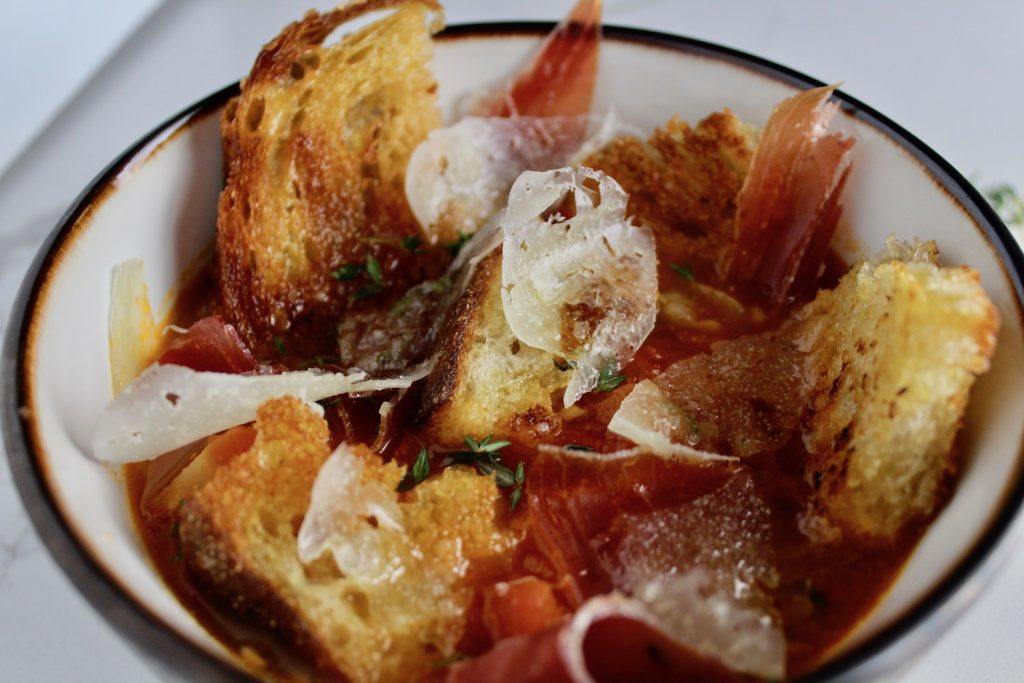 Side shot of Tomato Soup with Jamón and Manchego in a bowl on a white countertop