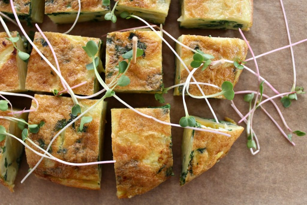 Top down shot of spanish tortilla with radish greens, cut into squares and topped with sprouts