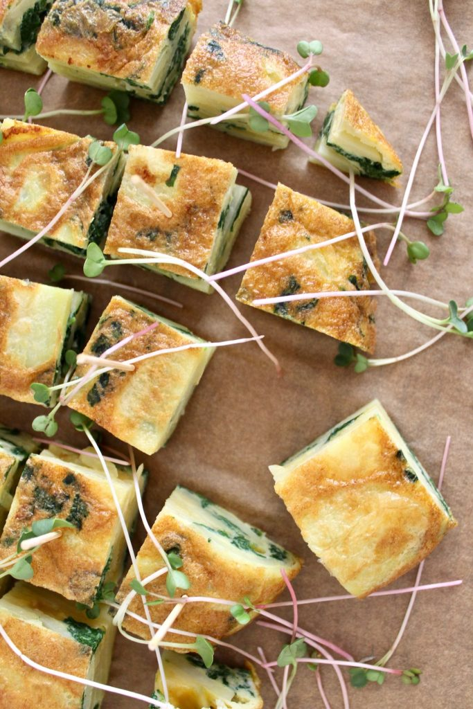 Top down shot of spanish tortilla with radish greens, cut into squares and topped with sprouts and one out of place