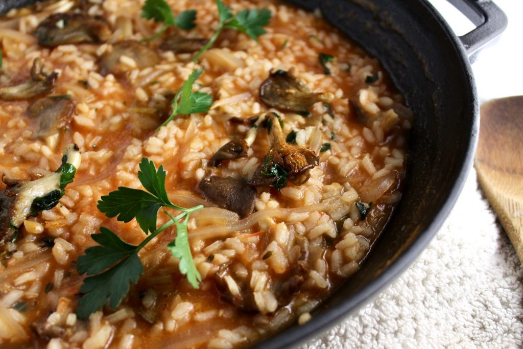 Close up of rice with wild mushrooms in a black pot