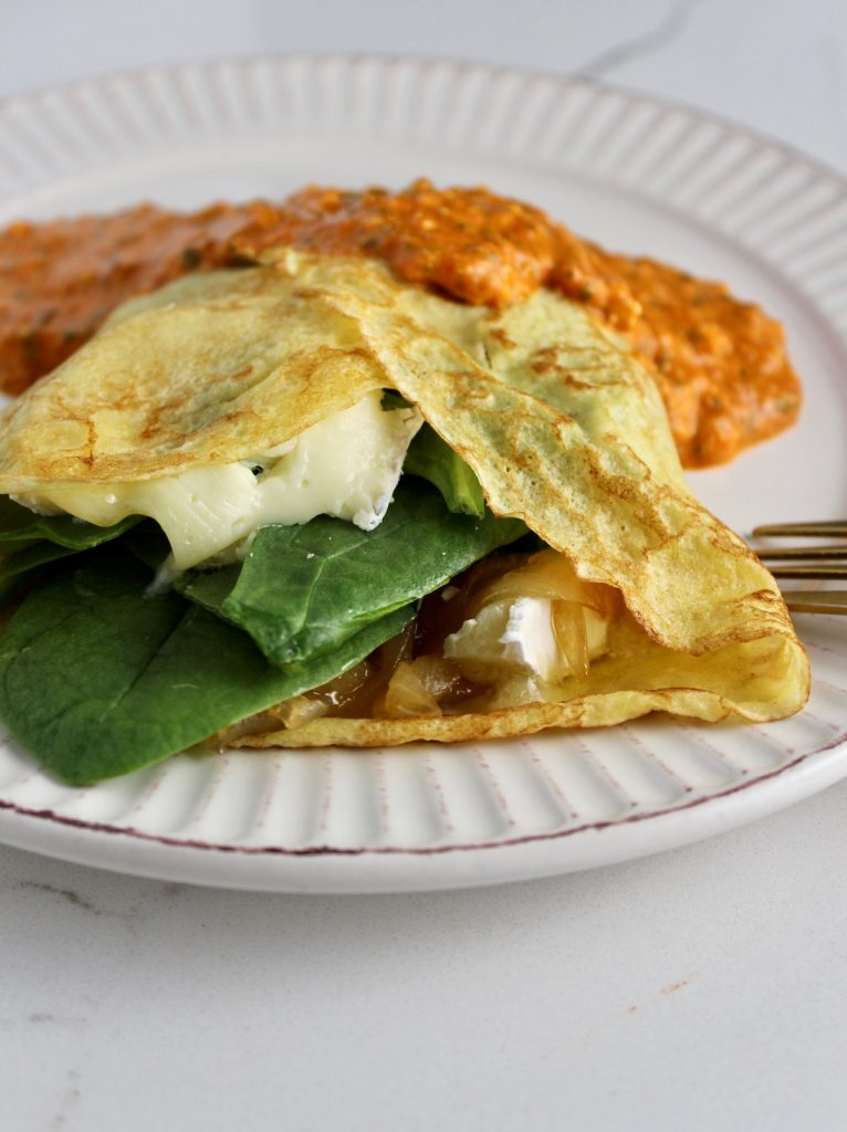 Side view of French Crepes with honey onions, brie, and spinach on top on a white plate