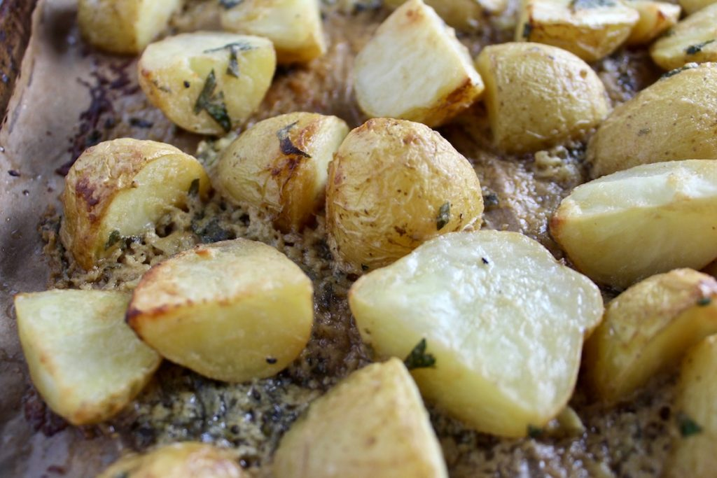 Close up view of Roasted Potatoes with Dijon Butter sitting on a pan