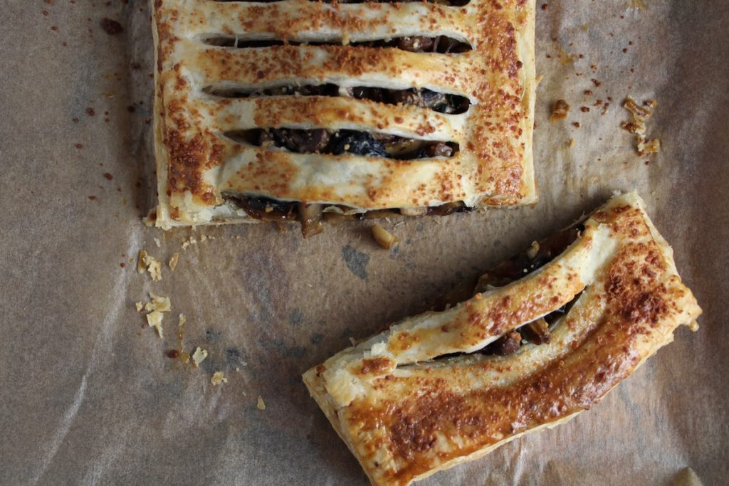 Cut open jalousie with mushrooms, ramps and onions sitting on parchment paper