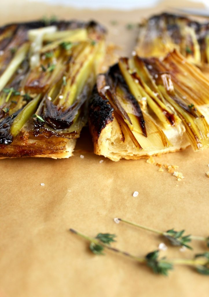 side view of caramelized leek tart cut into pieces on parchment paper