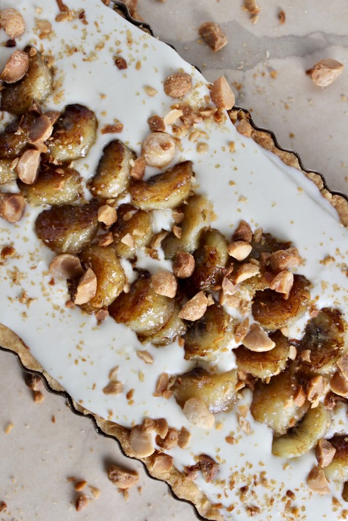 Top down shot of Macadamia Tart with Honey Cream on bornw parchment paper with macadamia nuts around the tart