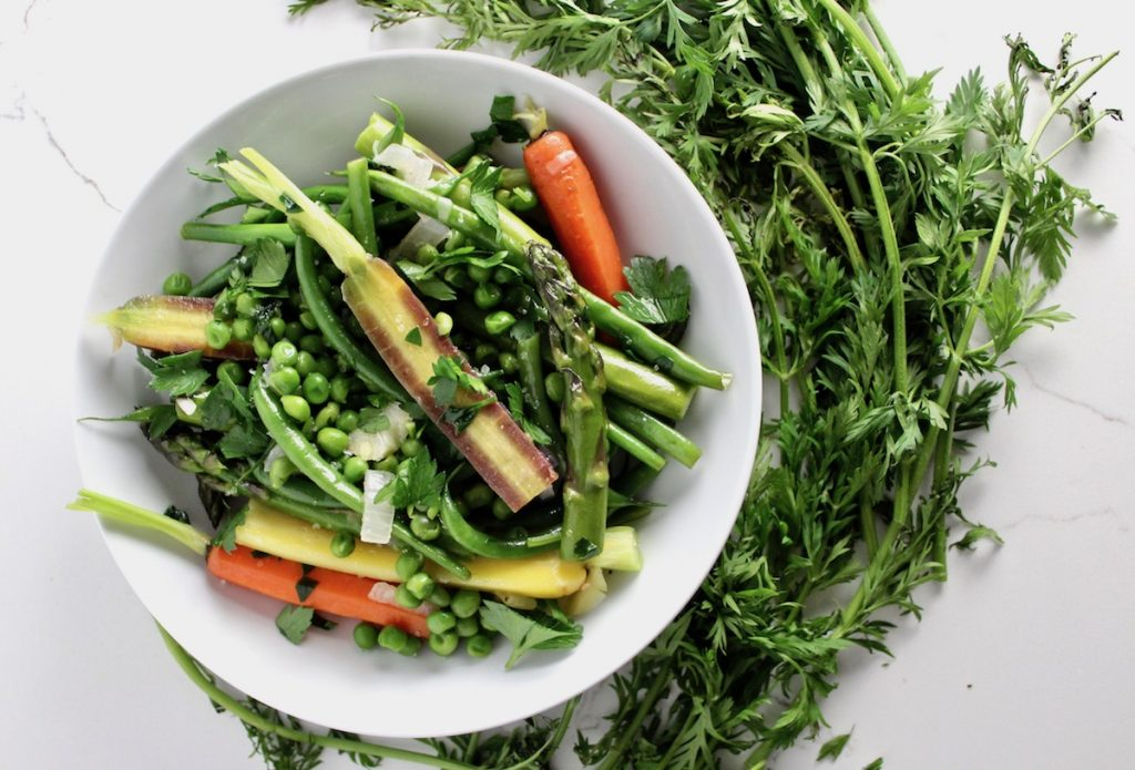 Sugar Glazed Spring Vegetable Jardinière in a white bowl next to green carrot tops