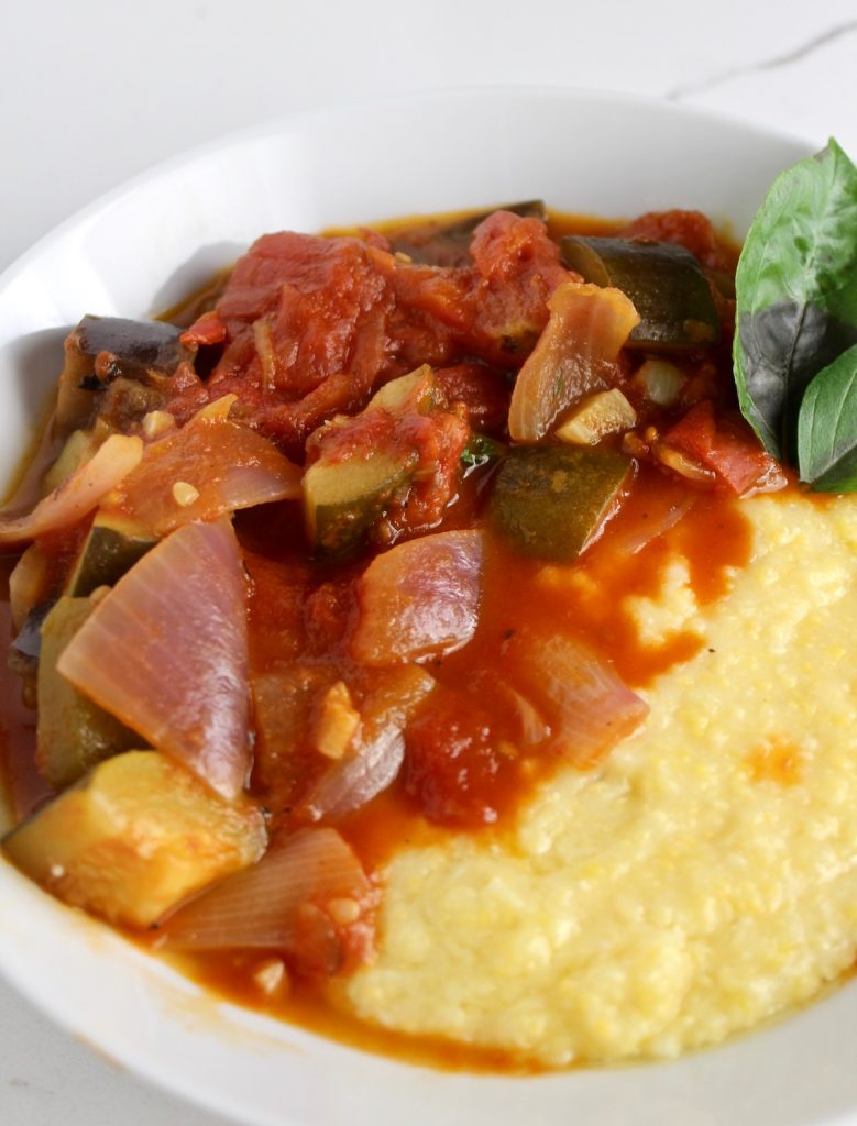 View of Ratatouille and Parmesan polenta sitting in a white bowl on a white countertop