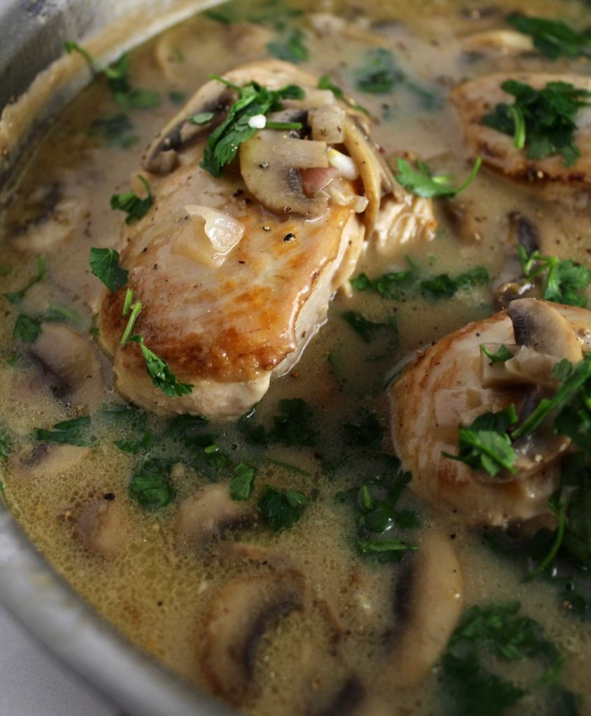 Top down shot of champagne chicken with mushrooms in a creamy sauce in a giant sauce pan on a white counter top