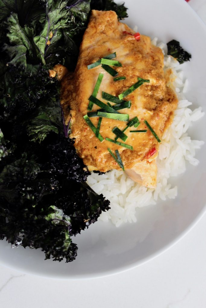 Top down shot of red curry slamon with roasted kale sitting on white rice in a white bowl on a white countertop