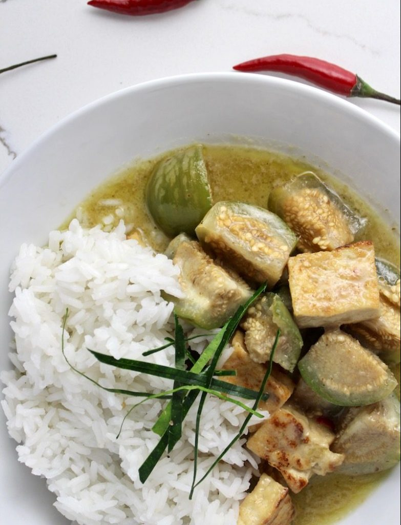 top down view of green curry with thai eggplants in a white bowl on a white countertop next to a red chile