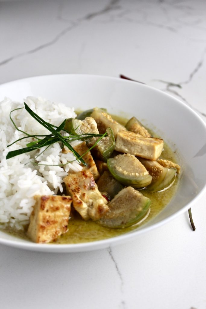 Side view of green curry with thai eggplants in a white bowl on a white countertop