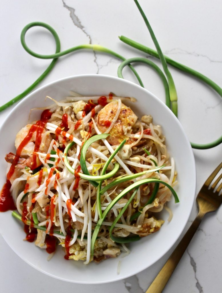 Top down shot of pad thai with garlic scapes in a white bowl on a white covertop next to garlic scapes and a gold fork