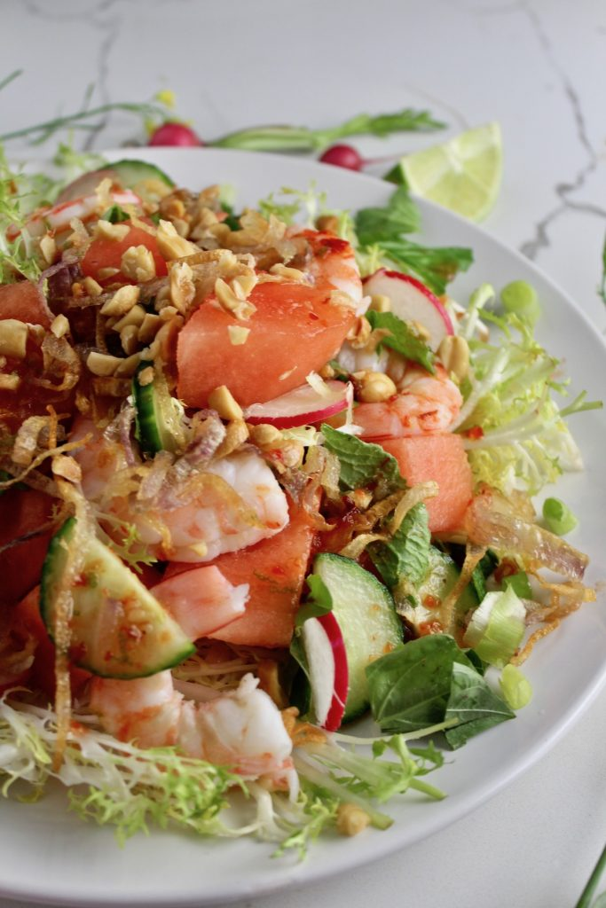 side view of thai watermelon salad on a white plate