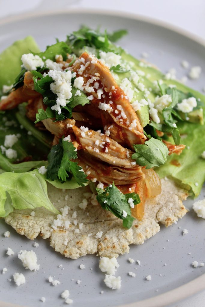 Side view of Chicken Tinga Tacos on a grey plate with lettuce and cheese