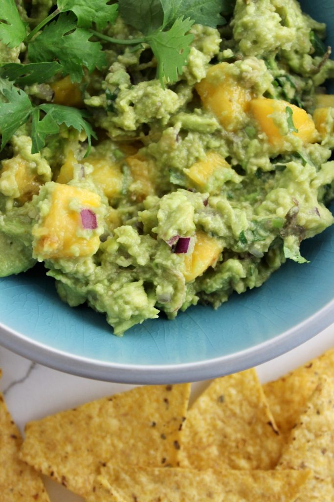 Top down shot of peachy guac in a blue bowl next to chips on a white countertop