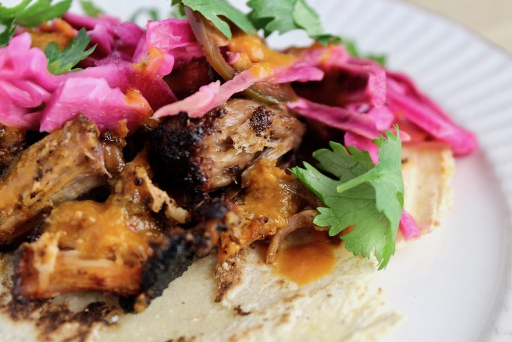 side view of top down shot of Smoked Carnitas in Peach Chipotle Sauce with Citrus Slaw on a tortilla