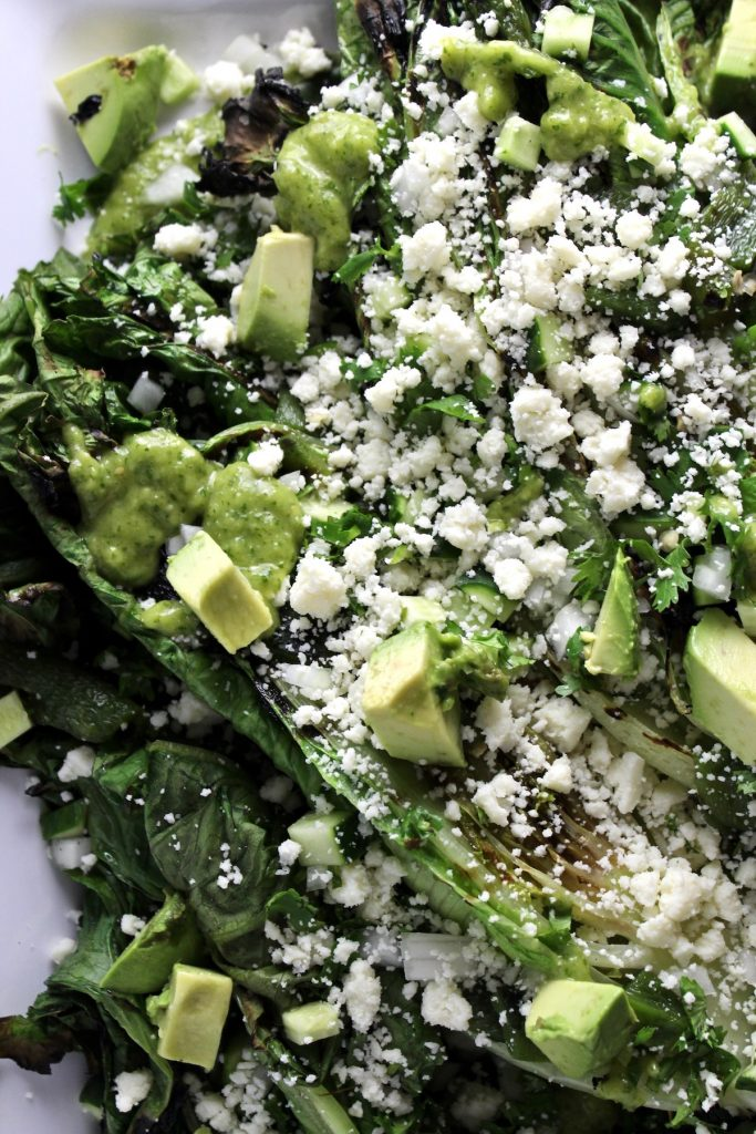close up of Grilled Romaine Salad with Tomatillo Dressing on a white platter on a white countertop