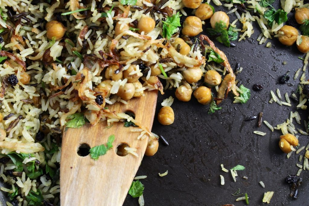 close up of herbed basmati and wild rice with currents and chickpeas with a wooden spoon