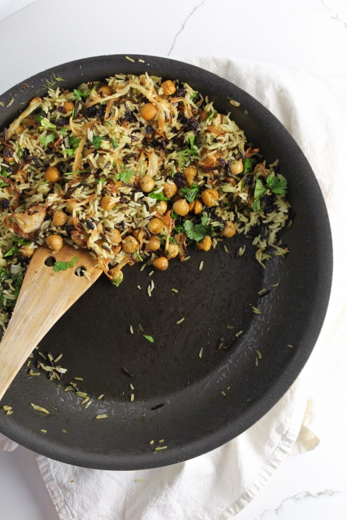top down shot of herbed basmati and wild rice with currents and chickpeas in a black pan with a wooden spoon