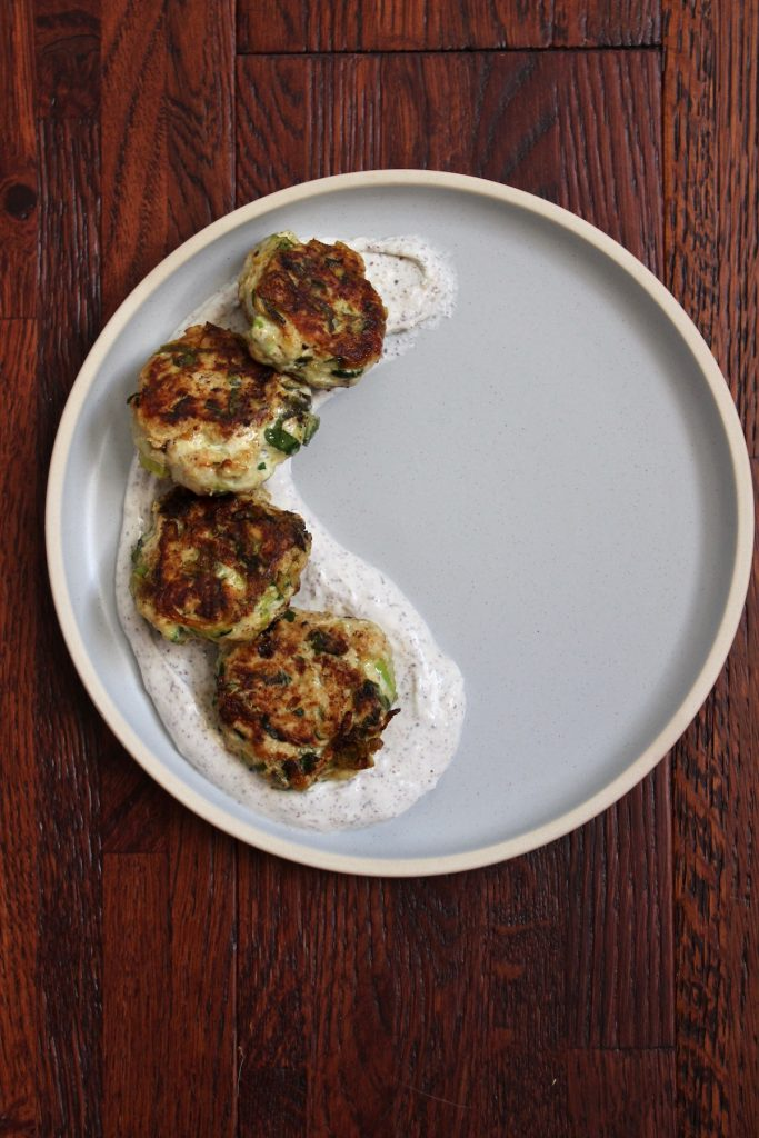 Turkey Zucchini Meatballs with Sumac Sauce on a blue plate on a wood counter