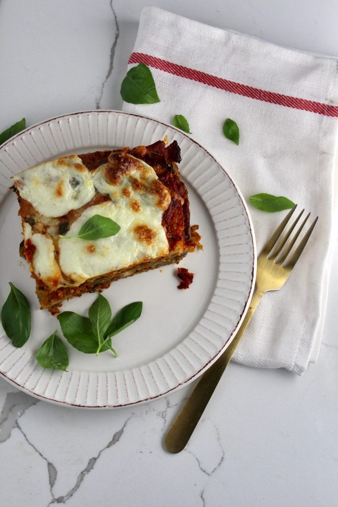 top view of eggplant Parmesan on a plate with basil next to a gold fork on a white napkin