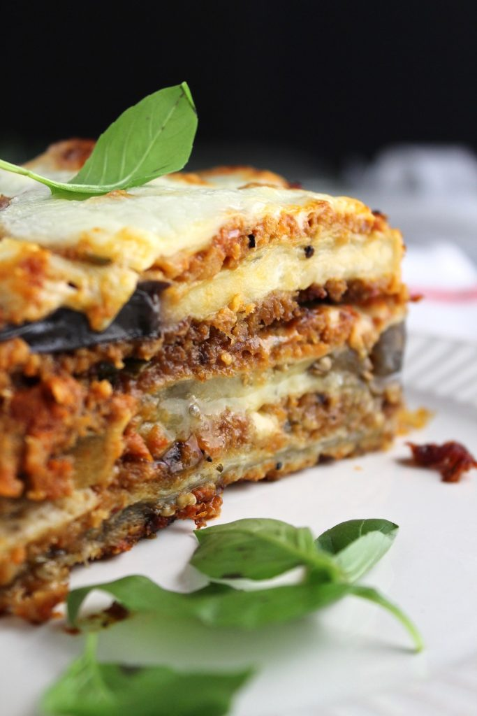 side view of eggplant parmesan layers with basil on a white plate