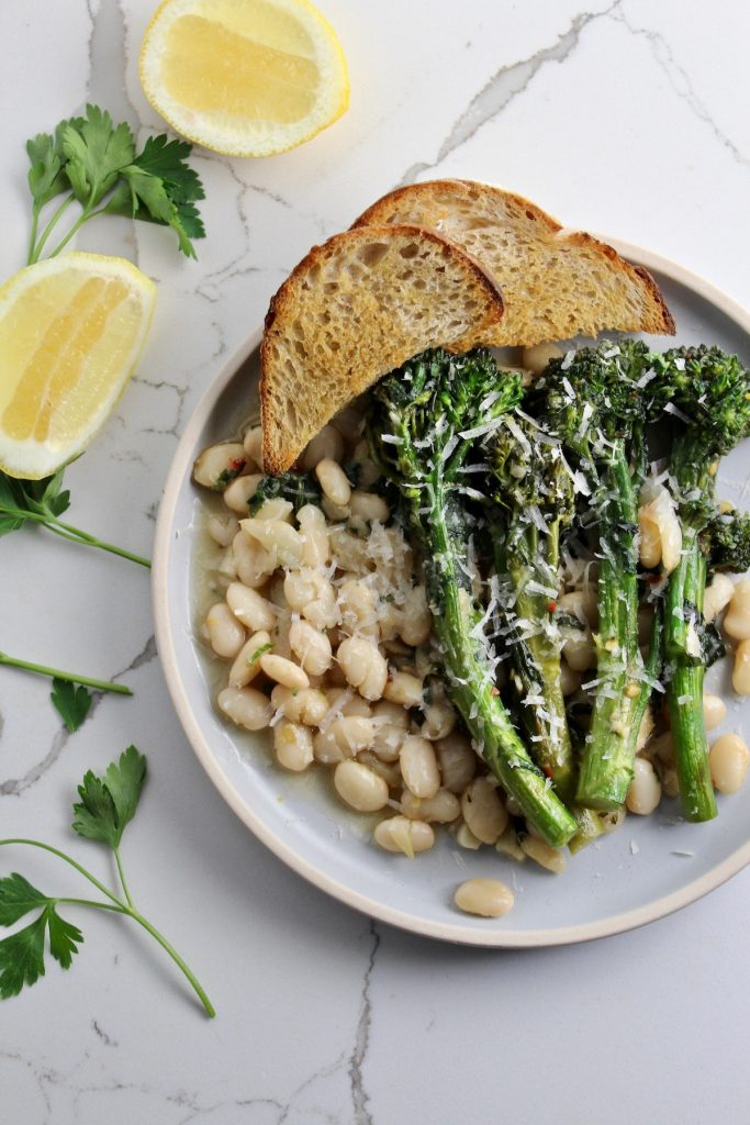 top down shot of white beans and broccolini next to bread , lemon and parsley