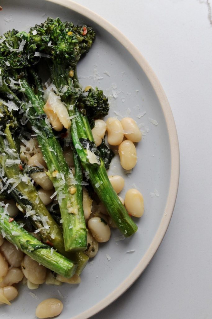 top down of broccolini and white beans on a blue plate