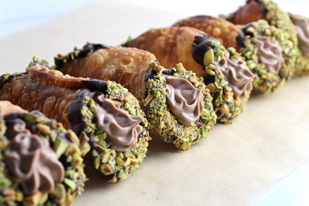 side view of cannoli with pistachios on parchment paper