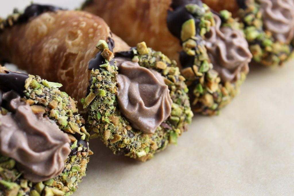 close up shot of cannoli with chocolate filling and pistachio outside