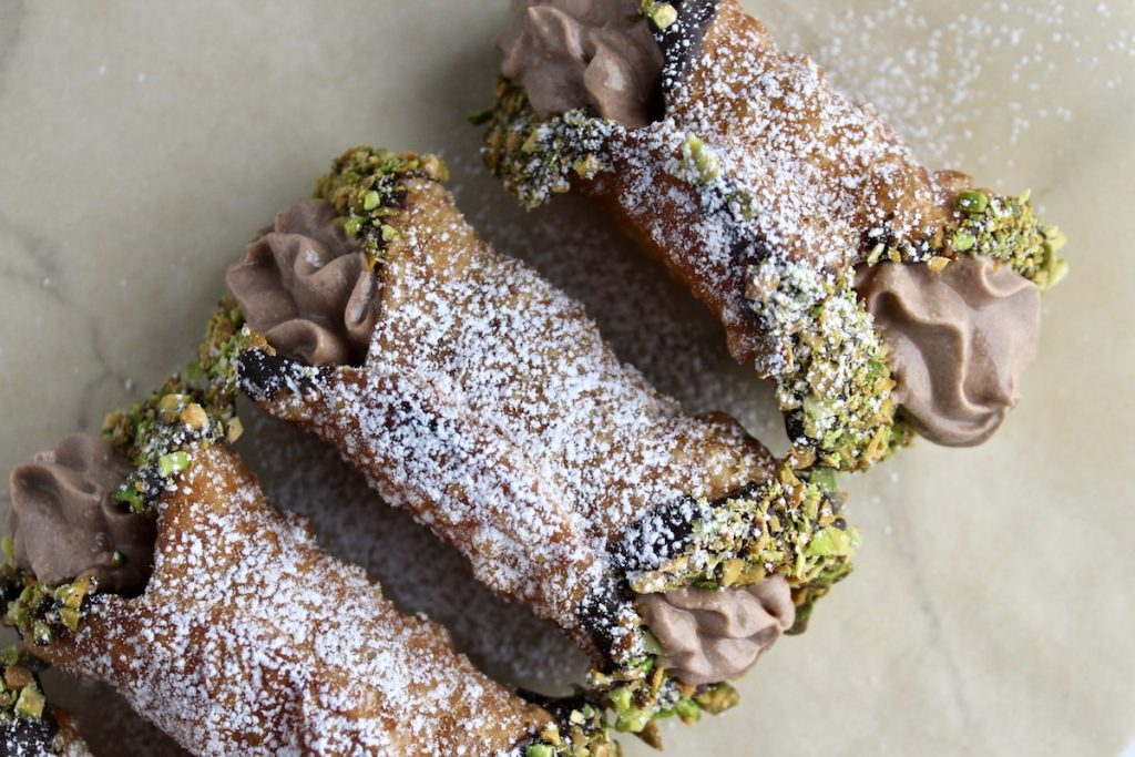 top down shot of 3 cannoli on parchment paper