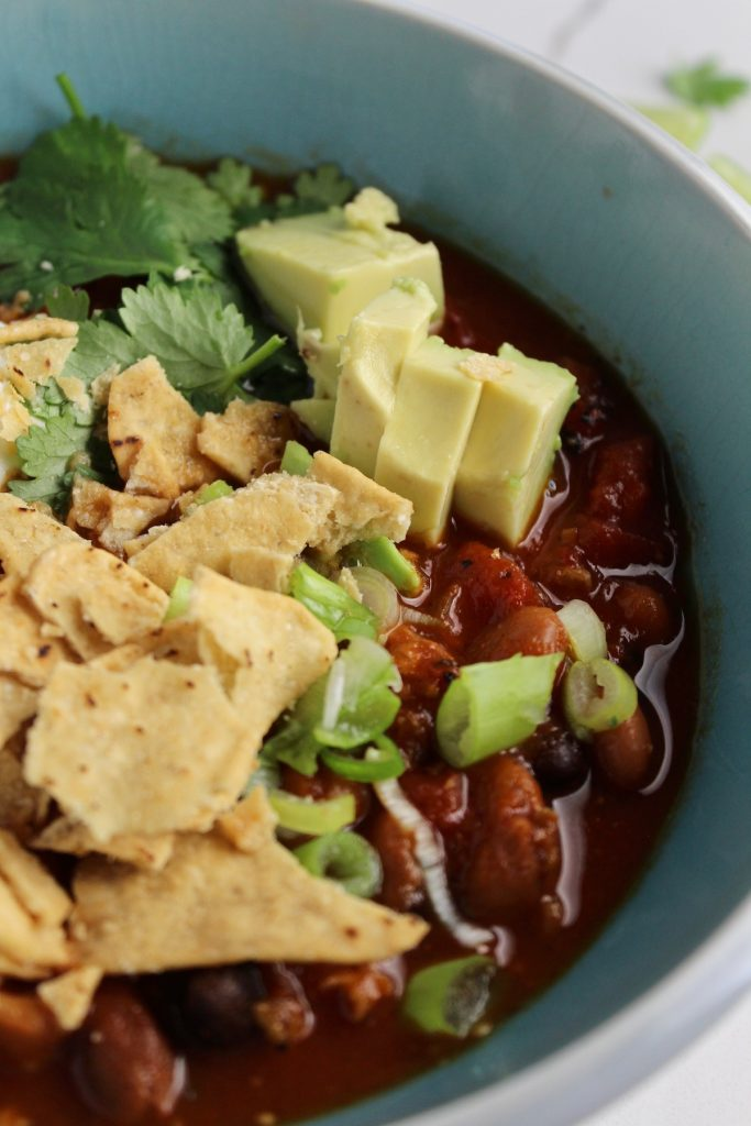 close up shot of beyond meat chili in a blue bowl with avocado and chips