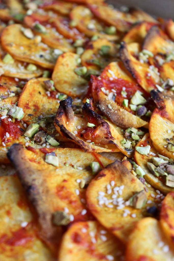 close up shot of harissa sweet potatoes with pistachios and seeds